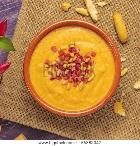 A square photo of salmorejo, traditional Spanish cold soup, with bread sticks and crumbs, shot from above on a burlap texture