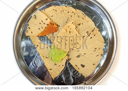 Indian bread served with traditional sauces, in the typical tableware. Shot from above on white background