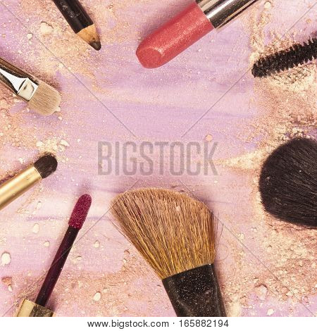 Makeup brushes, lipstick and pencil on a light purple background, with traces of powder and blush on it. A square template for a makeup artist's business card or flyer design, with copyspace