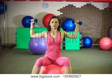Young Beautiful White Girl In A Pink Sports Suit Does Physical Exercises With Dumbells And A Fit Bal