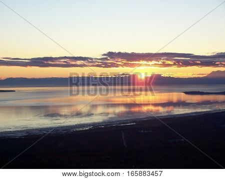 Amazing view of sunset or sunrise, overlooking the ocean, from the top of a mountain in Anchorage Alaska. Land silhouetted against a colorful morning or evening sky.