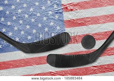 Hockey puck hockey sticks and a picture of the American flag on the ice. Concept