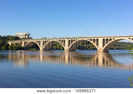 Key Bridge with reflection in Potomac River in Washington DC USA. Quiet waters of Potomac River in early morning near the scenic bridge.