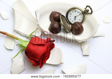 Shattered bowl with a rose and chocolates next to a pocket watch.