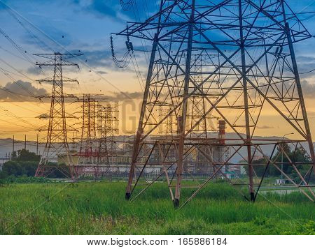 wilight photo of High voltage post or High voltage tower in green field and power plant at Butterworth, Penang, Malaysia