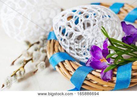 Traditional Czech easter decoration - white lacy knitted eggs in wicker nest with crocus flower and blue ribbon. Spring easter holiday arrangement.