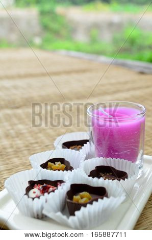Chocolate sweets in paper pumpkins with pink candle
