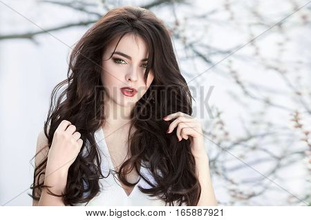 Sensual young girl standing in white dress at blossoming tree in the garden against white background. Beauty of woman and nature consept. Portrait of beautiful model with curly brown hair posing and looking at camera.