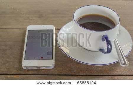Black coffee in white glass, telephone, on the table brown background.