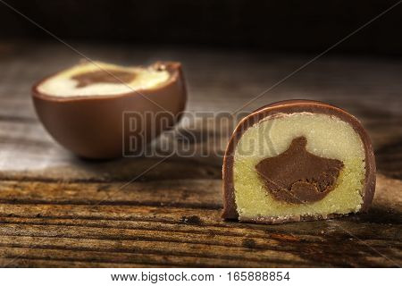 One round chocolate candy cut in half over wooden background