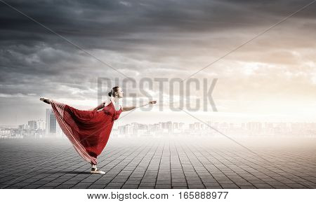 Passionate woman dancer in red dress reaching her hand