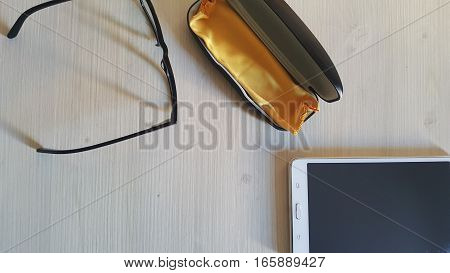 Top view on office desk table with glasses and tablet