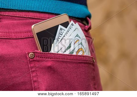 US dollar modern smartphone in red jeans pocket