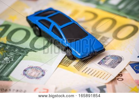 blue Toy car and euro bills macro