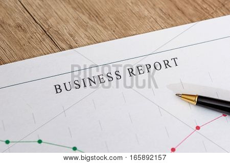 Analyzing financial chart with pen on desk