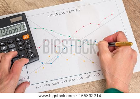 Male hand with pen and calculator on business chart