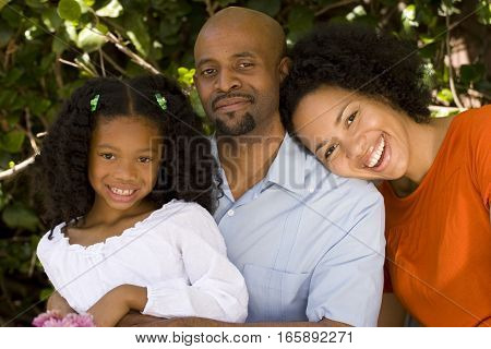 Happy African American parents and their daughter.