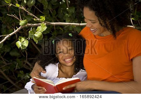 Happy African American parent reading with her child.