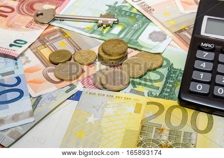euro banknote and coins with house key