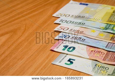different euro banknote on wooden table close up