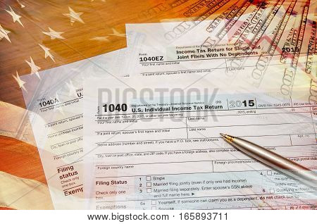 1040 tax form with american flag, pen