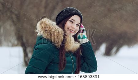 Young teenage girl playing with snow in park