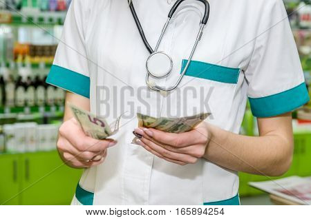 Female hands holding dollar banknotes at the pharmacy