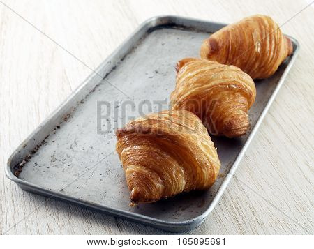croissant on oven tray and wooden table floor, French bread made from flour mixed with butter, roll a layer and baked