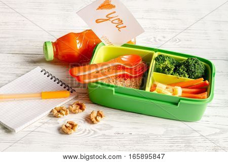 lunch box for kid with fresh vegetables on wooden background.