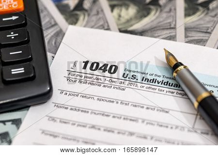 tax concept - money, pen, calculator, 1040 tax form