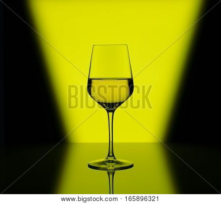 Wineglass with white wine on blurred multicolored background