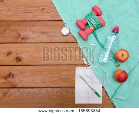 Bottle with towel water apples and skipping rope on wooden table background. Fitness lifestyle concept.