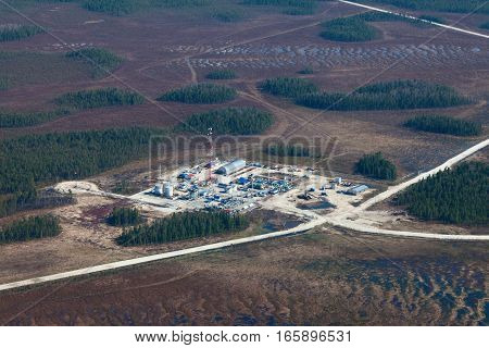 Aerial view over oilfield in marshy area in spring.