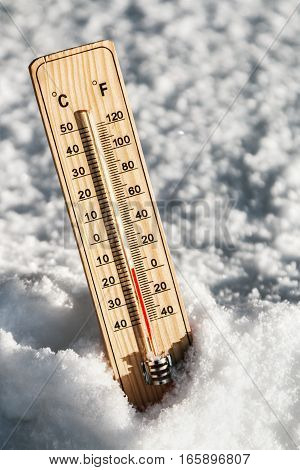 Wooden Thermometer in the snow with freezing temperatures
