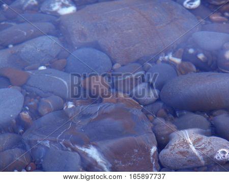 Pebbles seen through clear water. Usable as background
