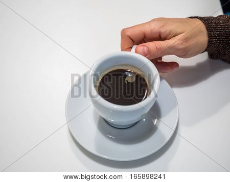 Top view of human's hand with cup of coffe standing on a saucer on white background. White cup with black coffee. Saucer with cup on white background.