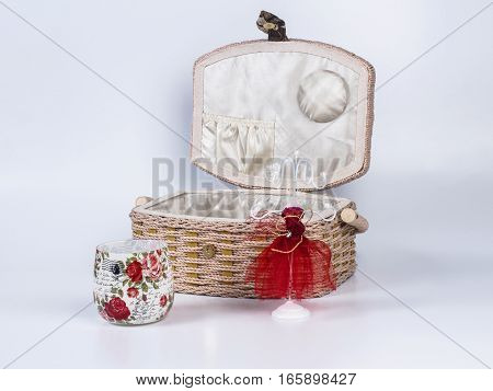 Composition of beige-coloured box with stand for bijouterie and candle in glass on white background. Handmade decoupage box. Red mannequin styled stand for bijouterie.