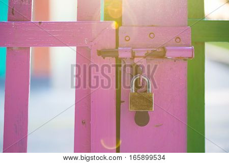 Pink color wood fence with safety lock in the morning with sun ray flair.