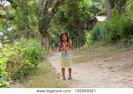 POPOTOTAN ISLAND PHILIPPINES - JANUARY 162012: Little girl goes on road in the Philippine village