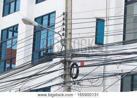 High voltage power pole with wires tangled on building background.
