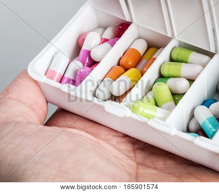 container with various pills in different colors. Focus on a green pill. soft focus