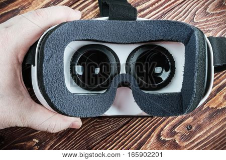 hand holding virtual glasses on a wooden background. Vignetting as an artistic effect