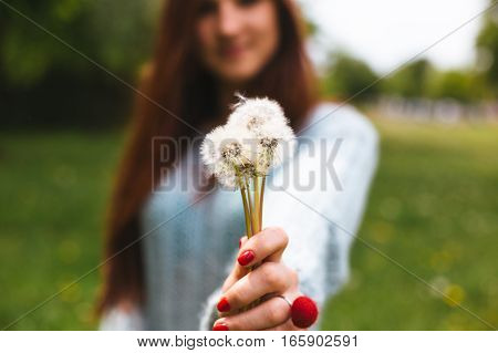 Pretty girl blowing dandelion in summer park. Happy relax time in the forest