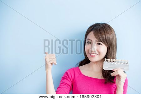 beauty woman hold teeth whitening tool and thumb upisolated on blue background