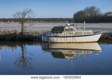 Motorboat on Royal town Ribe river in wintertime Denmark.