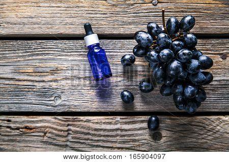 Essential oil of grape, vine, blue grapes, old wooden background, fruit. food