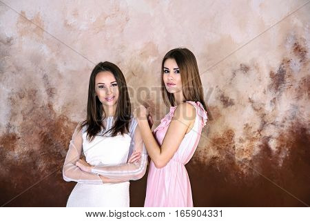 Two adult brunette sisters smiling holdind each otherand looking on camera