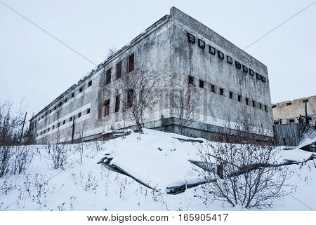 Exterior of housing of old decayed abandoned prison in Kolyma