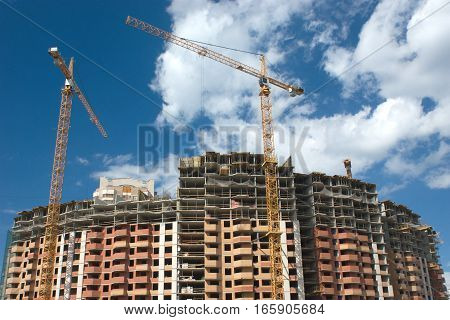 Tower hoisting cranes on residential building construction
