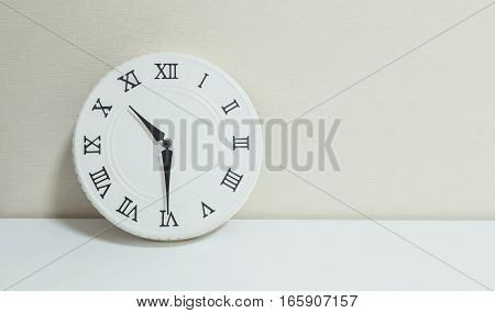 Closeup white clock for decorate show half past ten or 10:30 a.m. on white wood desk and cream wallpaper textured background with copy space